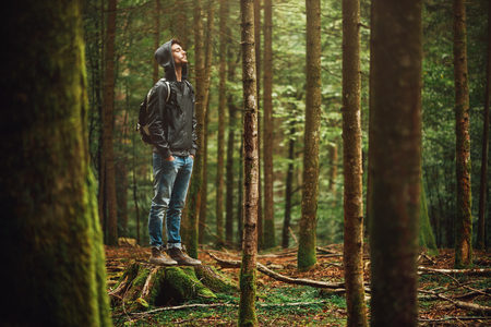 Photo for Hooded young man standing in the forest and exploring, freedom and nature concept - Royalty Free Image