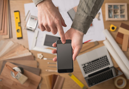 Photo pour Home decorator's hands holding a mobile touch screen phone, desktop with tools, laptop and wood swatches on background, top view - image libre de droit