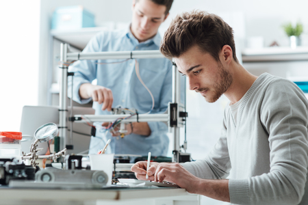 Photo for Engineering students working in the lab, a student is using a 3D printer in the background - Royalty Free Image