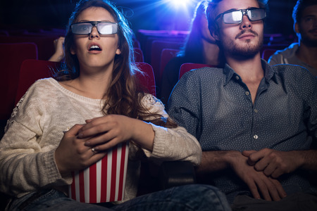 Photo pour Young teenagers at the cinema wearing glasses and watching a 3d movie, a girl is eating popcorn, entertainment and movies concept - image libre de droit