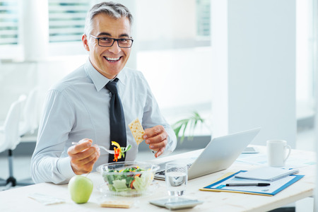 Smiling businessman sitting at office desk and having a lunch break, he is eating a salad bowl