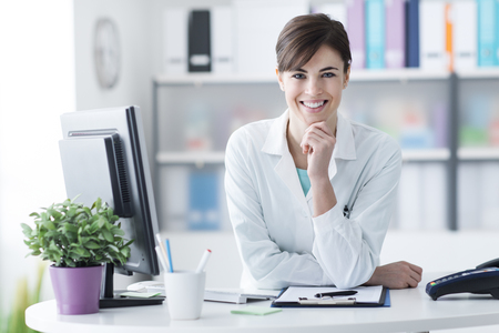 Foto de Attractive young female doctor leaning on the clinic reception desk with hand on chin, she is smiling at camera, medical staff and healthcare concept - Imagen libre de derechos