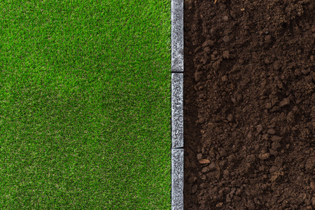 Fertile humus soil and lush grass divided by a stone edging, gardening and landscaping concept