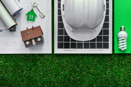 Photo pour Sustainable green building and energy saving concept: house project, solar panel and work tools on the grass, top view - image libre de droit