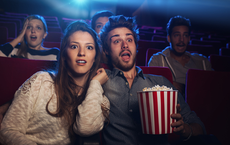 Young teenager couple at the cinema watching an horror movie