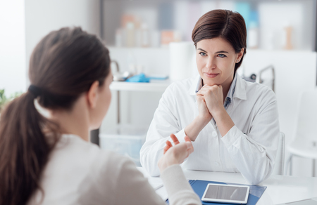 Foto de Doctor working in the office and listening to the patient, she is explaining her symptoms, healtcare and assistance concept - Imagen libre de derechos