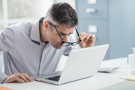 Photo for Businessman working at office desk, he is staring at the laptop screen close up and holding his glasses, workplace vision problems - Royalty Free Image