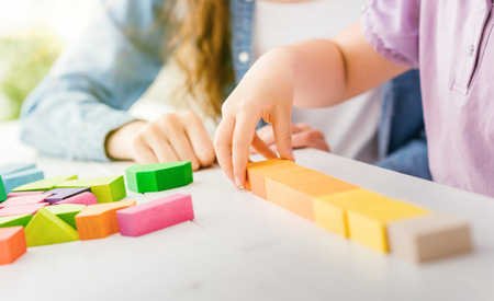 Foto de Girl playing with colorful toy wood blocks, her mother is helping her, education and fun concept - Imagen libre de derechos