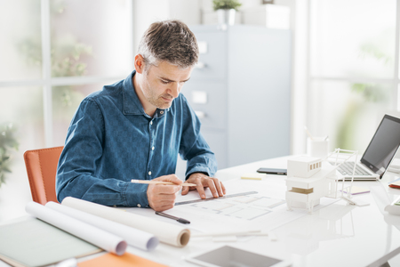Foto de Professional architect working at office desk, he is drawing and making measurements on a project blueprint, design and architecture concept - Imagen libre de derechos
