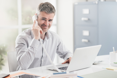 Photo pour Confident smiling businessman and consultant working in his office, he is having a phone call: communication and business concept - image libre de droit