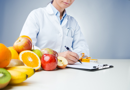 Foto de Professional nutritionist working at desk and writing medical records with fresh fruit on foreground - Imagen libre de derechos