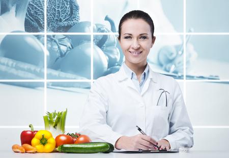Photo pour Smiling nutritionist writing medical prescriptions with fresh vegetables - image libre de droit