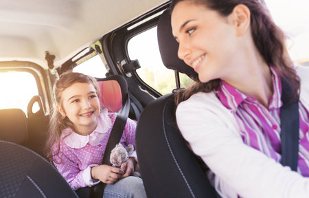 Foto de Cute young girl in a car with her mother, they are sitting and smiling at each other - Imagen libre de derechos
