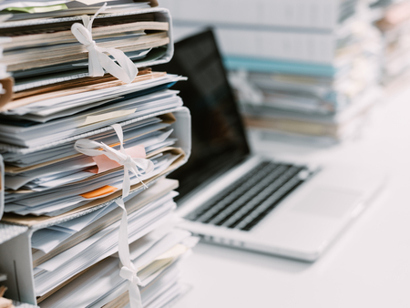 Foto de Piles of paperwork in the office and laptop on the desktop - Imagen libre de derechos