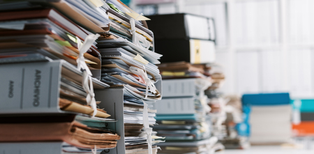 Foto de Stacks of paperwork and files in the office: work overload, files management and administration concept - Imagen libre de derechos
