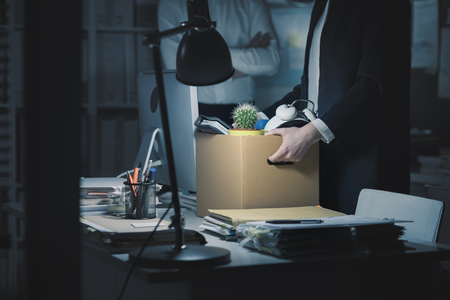 Photo pour Boss firing a young employee in the office, she is packing her belongings and holding a cardboard box - image libre de droit