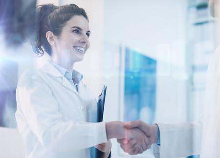 Foto de Young female practitioner shaking hands with a doctor, career and healthcare professionals concept - Imagen libre de derechos