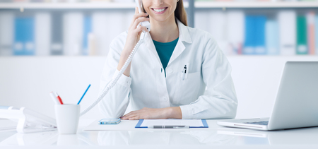 Photo pour Smiling female doctor working at office desk and answering phone calls, healthcare and consulting concept - image libre de droit