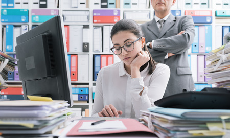 Photo pour Boss watching over his young employee and standing behind her, she is working and feeling oppressed - image libre de droit