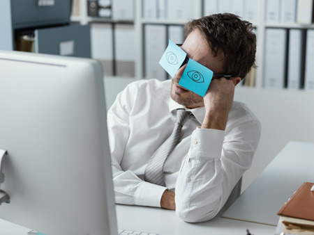 Photo pour Lazy unproductive office worker wearing funny sticky notes on his glasses and hiding his closed eyes - image libre de droit