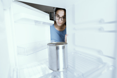 Photo pour Sad woman looking into her empty fridge with no groceries - image libre de droit