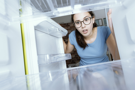 Photo pour Young hungry desperate woman looking into her empty fridge, she is panicking - image libre de droit