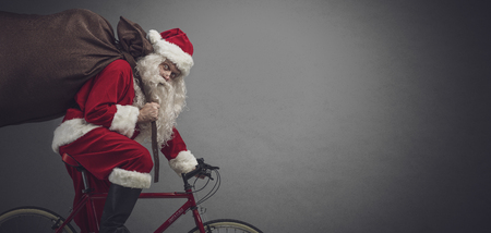 Foto de Santa Claus carrying a heavy sack with gifts for Christmas and riding a bicycle, banner with blank copy space - Imagen libre de derechos