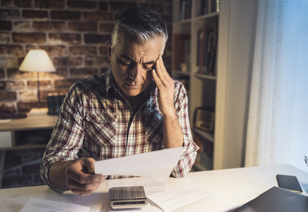 Photo pour Worried mature man checking his domestic bills at home, he is concerned and reading his financial statements - image libre de droit