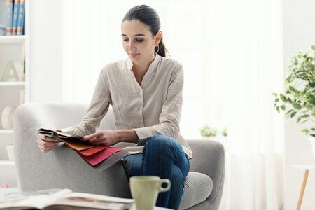 Photo pour Young woman choosing the best upholstery for the armchair - image libre de droit