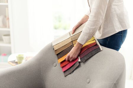 Photo pour Professional decorator choosing the best upholstery for the armchair - image libre de droit