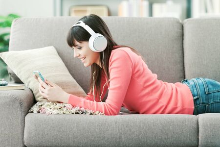 Photo pour Young smiling woman with headphones relaxing on the sofa and listening to music online using a smartphone - image libre de droit