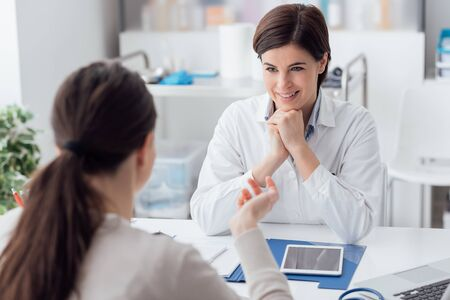 Photo pour Doctor working in the office and listening to the patient, she is explaining her symptoms, healtcare and assistance concept - image libre de droit