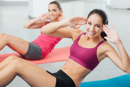 Photo for Smiling women exercising at gym on a mat and looking at camera, fitness and workout concept - Royalty Free Image