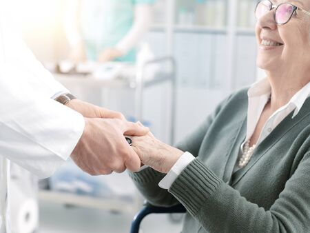Photo pour Professional doctor helping and supporting a senior patient on wheelchair, he is holding her hands, healthcare and geriatrics concept - image libre de droit