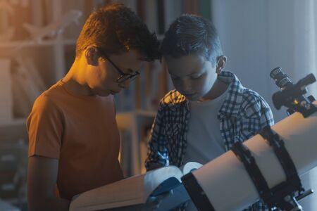 Photo for Smart kids using a telescope and studying astronomy together, they are searching informations in a book - Royalty Free Image