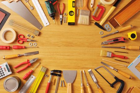 Photo for DIY and home improvement banner with work and construction tools on a wooden workbench top view, copy space at center - Royalty Free Image