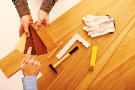 Photo pour Carpenter showing some wooden baseboard swatches to a customer and choosing a color, flooring installation and work tools on background - image libre de droit