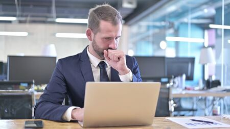 Photo pour The Young Businessman having Coughing while working on Laptop - image libre de droit