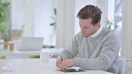 Photo pour Young Man Writing on Paper at Work - image libre de droit