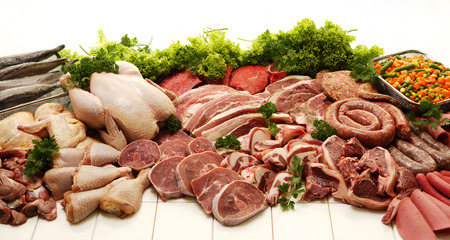 A display of various meats including chicken, steak, beef, fish, deli meats and boerewors on a white studio background