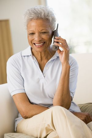 Woman sitting in living room using telephone and smiling