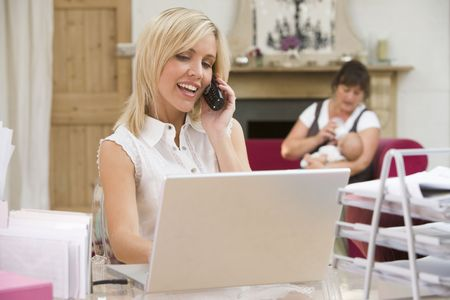 Woman in home office with laptop and telephone with mother and  in background