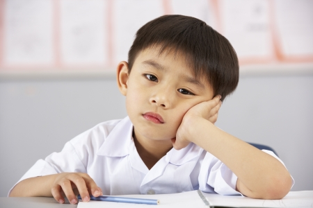 Unhappy Male Student Working At Desk In Chinese School Classroom