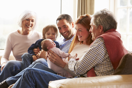 Multi Generation Family Sitting On Sofa With Newborn Baby