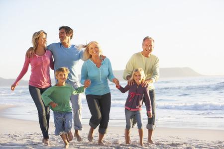 Three Generation Family On Holiday Running Along Beach