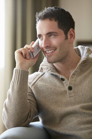 Young man talking on cordless phone at home