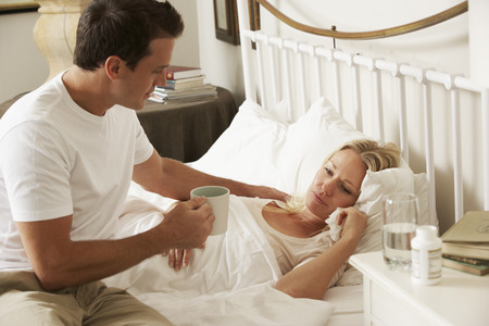 Husband Bringing Sick Wife Hot Drink In Bed At Home