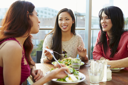Three Female Friends Enjoying Lunch At Rooftop Restaurant