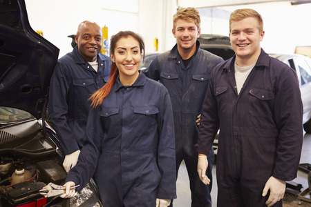 Teacher Helping Students Training To Be Car Mechanics