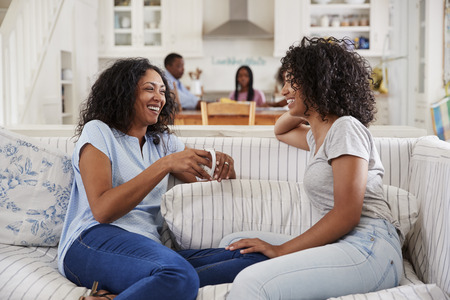 Photo pour Mother Talking With Teenage Daughter On Sofa - image libre de droit
